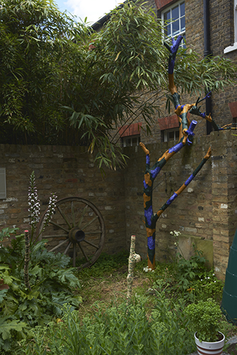 Rupert Ackroyd 'Cart Wheel Exercise' (with David Gates) 2014 (left), Rosa Nguyen 'Two Morris sticks' 2019, wall paper, paint, wood (centre),  Matt Hale 'Ceanothus no.31 Trunk series' 2019, Ceanothus tree (dead), acrylic paint, (right) photo by Andy Keate