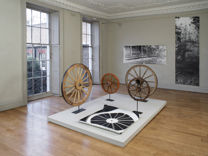 A Circle, image foreground:  Rupert Ackroyd + David Gates 'Cart Wheel Exercise' 2014, a group of 5 works as follows: (i) 112 cm dia, oak, elm, steel on steel base, (ii) 70 cm dia, perspex, oak, ash, elm, paint, steel on steel base, (iii) 111 cm dia, pine, chestnut, steel on steel base, (iv) 60 cm dia, pine, steel on steel base, (v) 106 × 120 cm, unique photogram on paper, base: 200 × 300 cm, mdf, pine, paint; background left: David Gates 'Standard Image #03' unique photograph 89 × 218 cm / 35 × 85.8 in (approx) 2014; background right:  David Gates 'Standard Image #10' unique photograph 292 × 89 cm / 114 × 25 in (approx) 2014; installation photography by Andy Keate