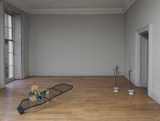 Domain, an exhibition by Mhairi Vari, installation view showing 'Shift' (mdf, dylon, van security grille, 70(h)×160×80cm 2011) on left and 'Retired Skitter Links' (a pair of Sycamore branches, link fencing wire, pin–heads, marbles, cable and reel, hot–melt glue, 90(h)×60×30cm 2011) on right, photo by Andy Keate