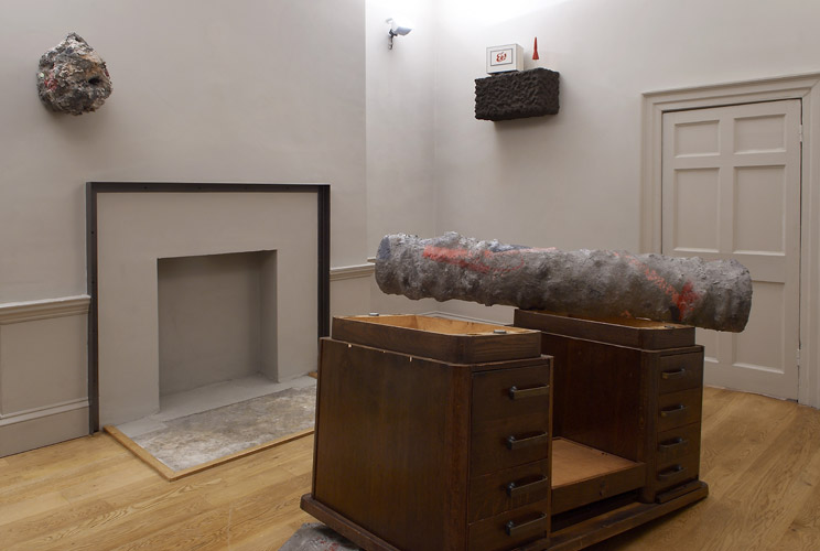 Phyllida Barlow and Steve Johnson 'Deep Time' 2009, from left to right: Phyllida Barlow, 'untitled: polystyrene, bonding plaster, cement, scrim, paint'              (40 h x 40 x 45 cm) 2009. Phyllida Barlow, 'Object for object series (ongoing since 1994) Object for an upturned desk 2009, cement over polystyrene, paint (130 h x 290 x 200 cm) Steve Johnson, 'Acht Uhr Drei�ig' 2009, mixed media (65 x 65 x 35 cm) go to Sharon Kivland's page